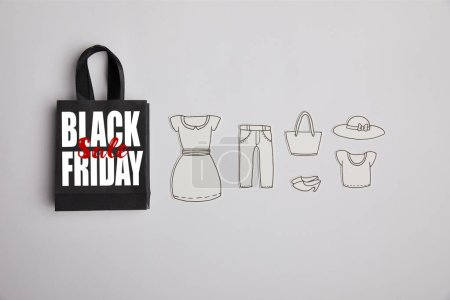 top view of black paper bag with black friday sale inscription and paper clothes on grey background