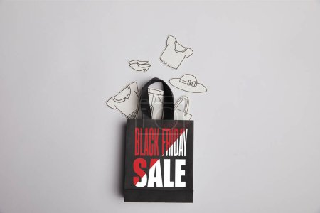 top view of paper bag with black friday sale inscription and paper clothes on grey background