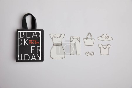 Photo for Top view of paper bag with black friday sale sign and paper clothes on grey background - Royalty Free Image