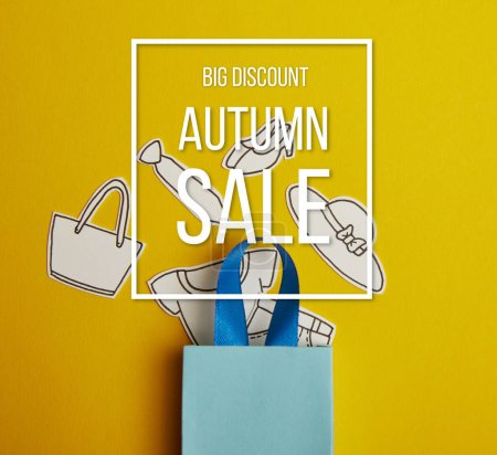 top view of blue shopping bag with paper clothes on yellow background, autumn sale inscription