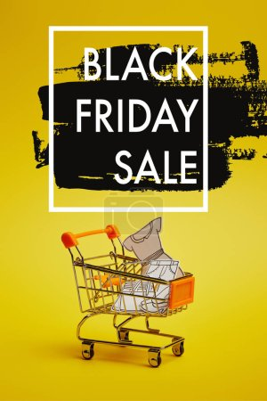close up view of little shopping trolley with paper clothes on yellow backdrop, black friday sale inscription