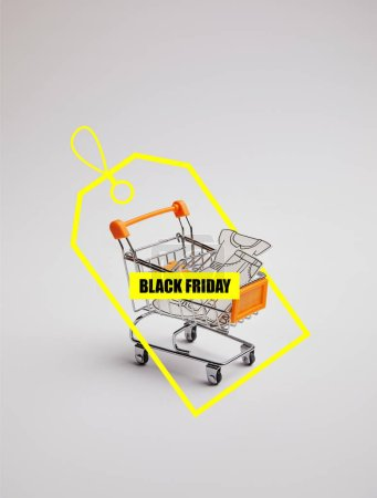 close up view of shopping cart with little goods made of paper on grey background, black friday sale tag