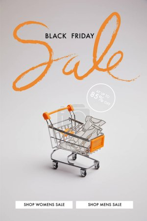 close up view of shopping cart with little goods made of paper on grey background, black friday sale inscription