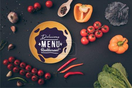 vue de dessus des poivrons et des tomates cerises avec une plaque jaune avec le lettrage de menu sur table gris