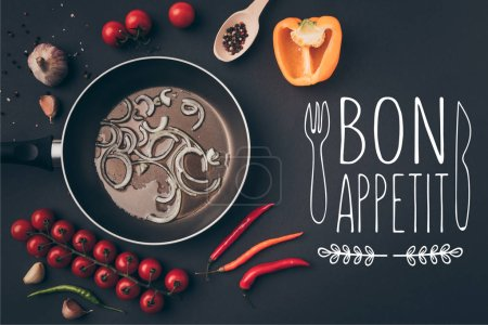 top view of frying pan with onion and oil among vegetables on gray table, bon appetit lettering