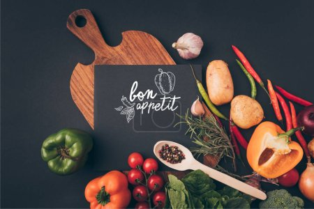 top view of black board on wooden table with vegetables on gray table, bon appetit lettering