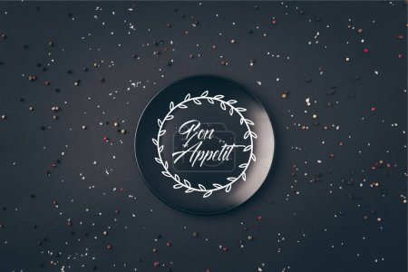 Photo for Top view of black plate with bon appetit lettering on gray table - Royalty Free Image