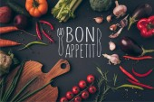 top view of different vegetables and cutting board on table with bon appetit lettering