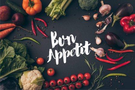 Foto de Vista superior de verduras sin procesar en mesa gris con bon appetit Letras - Imagen libre de derechos