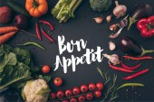 top view of unprocessed vegetables on gray table with bon appetit lettering