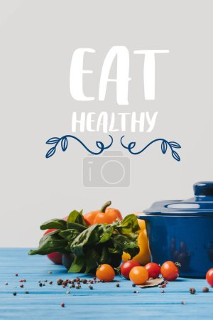 Photo for Pan with ripe organic vegetables on table, eat healthy lettering - Royalty Free Image