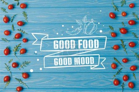Photo pour Haut de la page vue des tomates cerises avec roquette sur table bleue, lettrage de bonne humeur bonne nourriture - image libre de droit