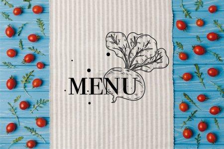 Photo pour Haut de la page vue de serviette et les tomates cerises avec roquette sur table bleue, lettrage de menu - image libre de droit