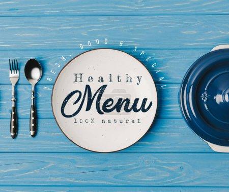 Photo pour Vue du dessus de la fourchette, cuillère et assiettes sur la table bleue, lettrage de menu sain - image libre de droit