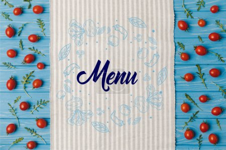 top view of napkin and cherry tomatoes with arugula on blue table, menu lettering