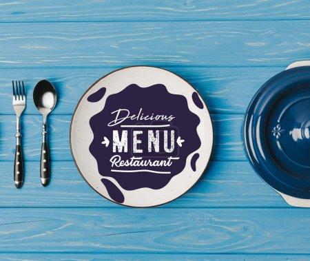 haut de la page vue de fourchette, cuillère et plaques sur table bleue, lettrage restaurant délicieux menu