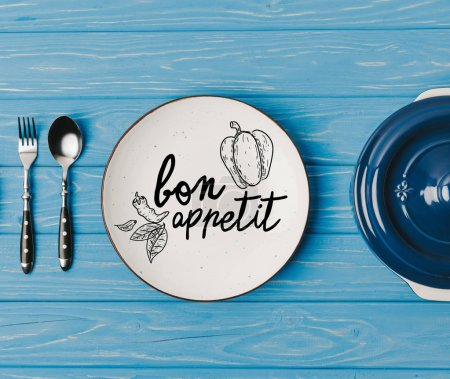 Photo for Top view of fork, spoon and plates on blue table, bon appetit lettering - Royalty Free Image