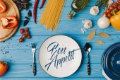 top view of ingredients for cooking pasta on blue table, bon appetit lettering