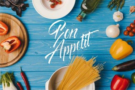 Photo pour Haut de la page vue des pâtes alimentaires non cuites et des légumes sur table bleue, bon appetit lettrage - image libre de droit