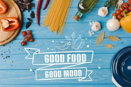 Photo pour Haut de la page vue des ingrédients pour la cuisson des pâtes sur table bleue, lettrage de bonne humeur bonne nourriture - image libre de droit