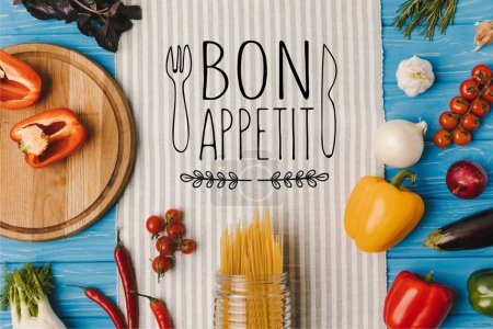 Foto de Vista de pasta sin cocer y vegetales maduros en servilleta en la mesa azul, superior bon appetit Letras - Imagen libre de derechos