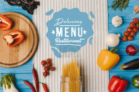 top view of uncooked pasta and ripe vegetables on napkin on blue table, delicious menu restaurant lettering