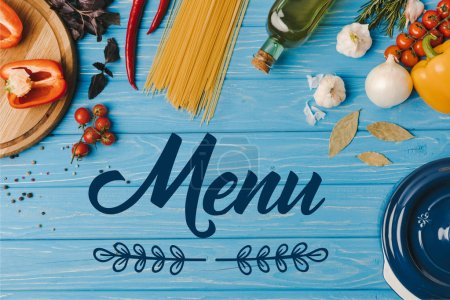 top view of ingredients for cooking pasta on blue table, menu lettering