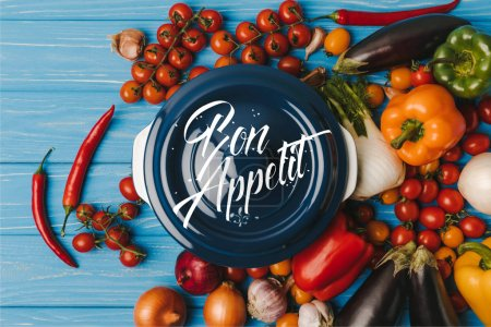 top view of pan between vegetables on blue table, bon appetit lettering