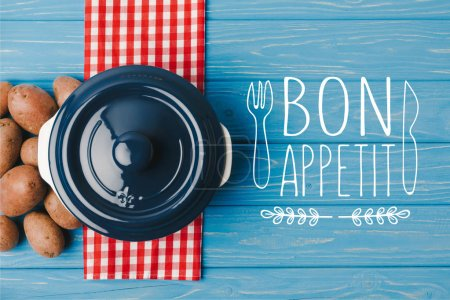 top view of pan and potatoes on blue table, bon appetit lettering