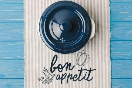 Photo for Top view of pan on napkin on blue wooden table, bon appetit lettering - Royalty Free Image