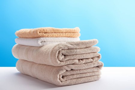 close-up view of stacked clean towels on white table on blue
