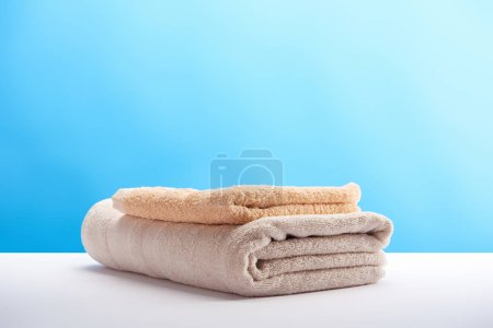 Photo for Stacked clean towels on white table on blue background - Royalty Free Image
