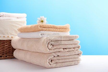 Foto de Pila de toallas suaves limpias, flor de manzanilla y cesta de lavandería en azul - Imagen libre de derechos