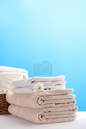 close-up view of towels, beautiful chamomile flower and laundry basket on blue