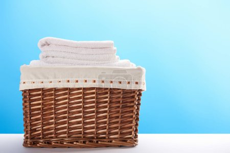 Photo for Close-up view of laundry basket with clean soft towels on blue background - Royalty Free Image