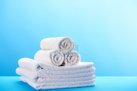 Photo for Rolled and stacked clean white towels on blue - Royalty Free Image