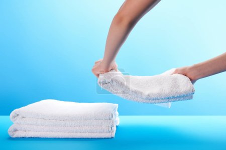 partial view of person stacking clean soft white towels on blue