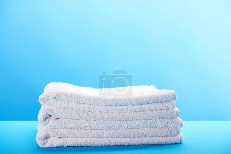Photo pour Tas de douces propre serviettes blanches sur fond bleu - image libre de droit