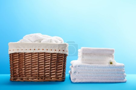stacked white clean towels with chamomile flower and laundry basket on blue