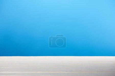 empty white wooden surface and bright blue background