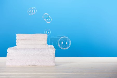 close-up view of clean white towels and soap bubbles on blue background