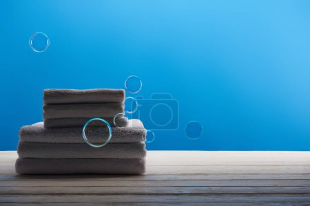 clean white towels and soap bubbles on blue background