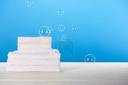 close-up view of clean soft white towels and soap bubbles on blue background