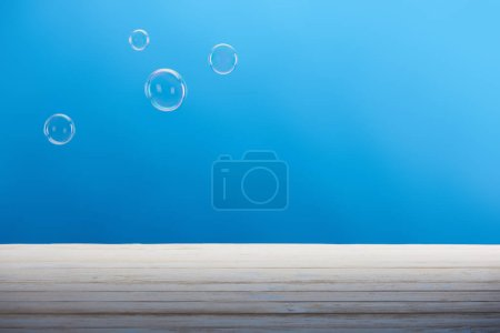 clean soap bubbles and white surface on blue background