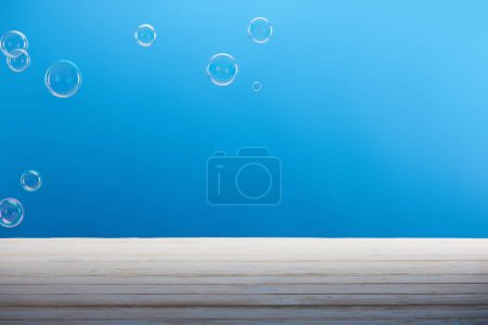 soap bubbles and white surface on blue background