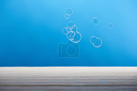 soap bubbles and white wooden surface on blue background