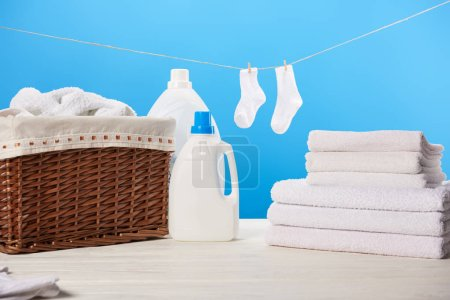 Wäschekorb, Plastikbehälter mit Waschflüssigkeiten, Stapel sauberer weicher Handtücher und weiße Socken, die an Seilen auf blauem Grund hängen