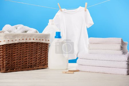 plastic containers with laundry liquids, laundry basket, pile of towels and clean white clothes hanging on rope on blue