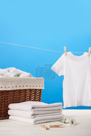 laundry basket, pile of clean towels, clothespins, chamomile flower and white t-shirt hanging on clothesline on blue
