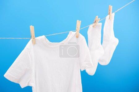 Photo pour Chaussettes blanches propres et t-shirt suspendu sur corde à linge isolé sur bleu - image libre de droit